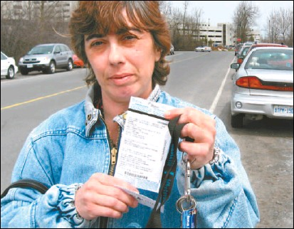 ?? GLEN MCGREGOR, THE OTTAWA CITIZEN ?? Virginia Baelde shows the $45 ticket she got for parking on Lynda Lane near the Ottawa Hospital's General campus. City officials suggest the rate of ticketing around the hospital simply reflects the fact that it is a high-traffic area.