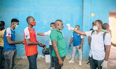 ?? DIEU NALIO CHERY/AP ?? Health ministry workers check the temperatur­e of fans entering a stadium before a soccer match March 25 in Port-au-Prince, Haiti.