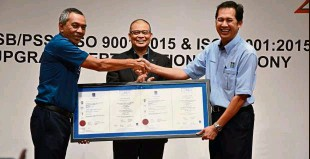 ??  ?? Dr Zahari (left) receiving the ISO certifications from Mohd Azanuddin while Aminar cheers on.