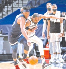?? - AFP photo ?? Josh Okogie #20 of the Minnesota Timberwolves and Kevin Durant #7 of the Brooklyn Nets go for a loose ball on April 13, 2021 at Target Center in Minneapolis, Minnesota.