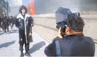 """?? Courtesy of Michael Hurt ?? Michael Hurt is seen photographing an """"mpromptu model"""" outside Dongdaemun Design Plaza. His setup includes large strobe lights, which he instructs photographers how to use in his four-session class."""
