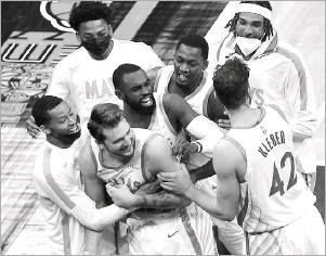 ?? Brandon Dill/the Associated Press ?? Luka Doncic (front center) and his Mavericks teammates celebrate his game-winning 3-point shot as time expired against the Memphis Grizzlies. It was the second time in his Mavericks career that he has won a game at the buzzer with a 3-pointer.