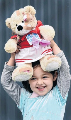 ?? PHOTO: PETER MCINTOSH ?? Bearing up . . . Santia Throp (3) happily holds aloft her bandaged bear after going to the Teddy Bear Hospital in Dunedin on Saturday.