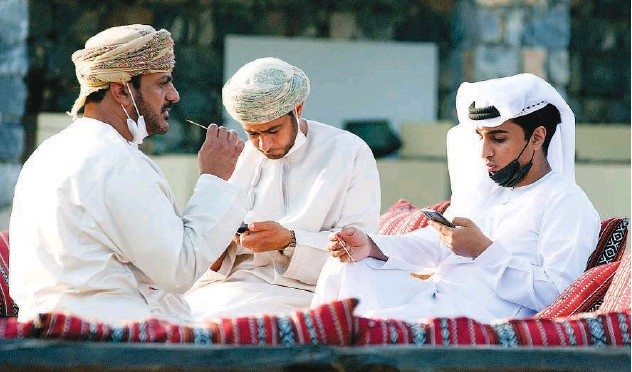 ?? Kamal Kassim/gulf Today ?? ↑ These men are engrossed in connecting with their mobile devices.