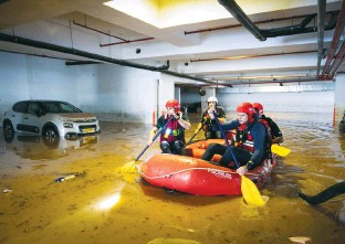 ?? (Yossi Aloni/Flash90) ?? FIREFIGHTERS row through a flooded parking lot in Ness Ziona last year.