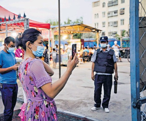 ??  ?? Uyghurs scan a QR code in order to enter a food market in Kashgar, Xinjiang