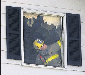 ?? BOB BROWN/TIMES-DISPATCH ?? A Chesterfield County firefighter examined damage after a house fire early Friday that claimed four lives and left three more injured.