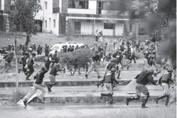 ?? — AFP ?? Pakistani police run from Opposition protesters during clashes near the Prime Minister's residence in Islamabad on Monday.