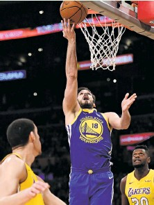 ?? Harry How / Getty Images ?? Warriors forward Omri Casspi (18) lays the ball up during Monday's overtime victory over the Lakers in Los Angeles.