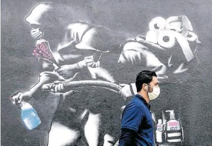 ?? Foto: Efe ?? Una persona pasea delante de un mural alegórico sobre el coronavirus.