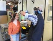 ??  ?? Sean Convery does pre-screening of associate Monica Gutierrez before beginning her work day at METALfx in Willits.