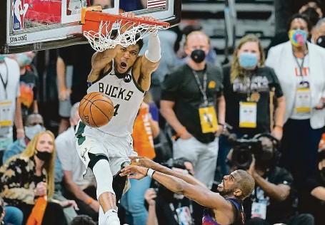 ?? FOTO ČTK/AP ?? Rozhodnuto. Lídr Milwaukee Janis Adetokunbo právě zasmečoval vítězný koš, bránící legenda Phoenixu Chris Paul jej navíc ještě fauloval.