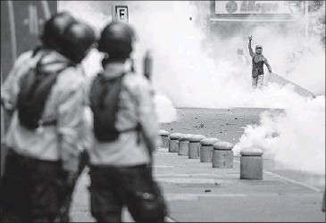 ?? Cristian Hernandez European Pressphoto Agency ?? DEMONSTRATORS clash with police in Caracas, Venezuela's capital. The nation has been roiled by food scarcities, soaring inf lation and weeks of bloody street protests calling for President Nicolas Maduro's ouster.