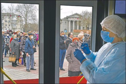 ?? (AP/Alexander Polegenko) ?? A Russian medical worker prepares a shot of Russia's Sputnik V coronavirus vaccine as people line up to at a mobile vaccination center in Simferopol, Crimea.