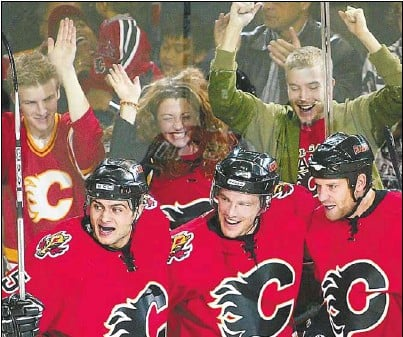 ??  ?? Mark Giordano, from left, Andrew Ference and Marcus Nilson have the backing of Flames fans after Nilson's goal late in the second period Saturday night at the Saddledome in Calgary's NHL home opener.