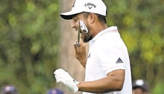 ?? CHARLIE RIEDEL | Associated Press ?? Xander Schauffele bites his club after his second tee shot on 16, the hole that killed his Masters hopes.
