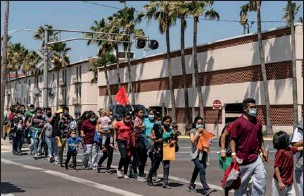 ?? GO NAKAMURA / AP ?? Asylum-seeking migrant families walk to a temporary shelter run by a local charity organizati­on after undergoing tests for the coronaviru­s in McAllen, Texas, on Thursday.