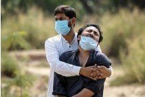 ?? REUTERS ?? A MAN is consoled by his relative as he sees the body of his father, who died from the coronavirus disease 2019 (COVID-19), before his burial at a graveyard in New Delhi, India, April 16.