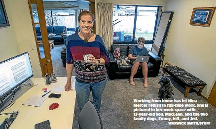 ?? WARWICK SMITH/STUFF ?? Working from home has let Nina Mercer return to full-time work. She is pictured in her work space with 13-year-old son, Maclean, and the two family dogs, Emmy, left, and Jed.