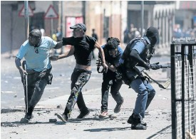 ?? Picture: Alaister Russell ?? Police attempt to arrest a protestor while being pelted with rocks during unrest in Westbury, Johannesburg, this week.