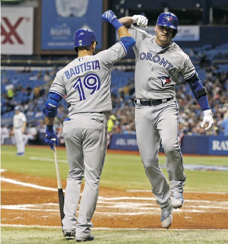 ?? BRIAN BLANCO/GETTY IMAGES ?? Toronto Blue Jays third baseman Josh Donaldson celebrates with Jays outfielder Jose Bautista after hitting a home run off Tampa Bay Rays starting pitcher Drew Smyly during the fifth inning on Monday in St. Petersburg, Fla. The homer was Toronto's third...
