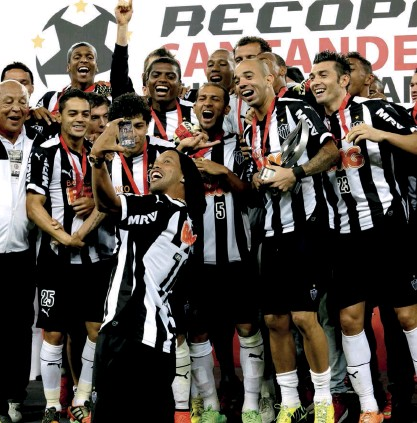 ??  ?? Below Ronnie takes a selfie with the rest of the Atletico Mineiro team after winning the 2013 Copa Libertadores; the Brazilian idol is keen to delve into the music business