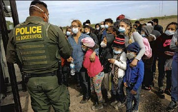 ?? Carolyn Cole Los Angeles Times ?? YOUNG ASYLUM SEEKERS wait in La Joya, Texas, for U.S. Border Patrol agents to bus them to processing facilities last month, when a record of nearly 19,000 minors were detained as they crossed the border alone.