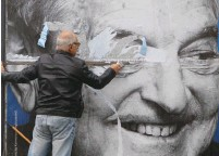 ?? (Bernadett Szabo/Reuters) ?? AN ACTIVIST of the Egyutt opposition party removes a government billboard displaying George Soros in Budapest in October.