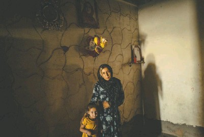 ?? PHOTOS BY NICOLE TUNG FOR THE WASHINGTON POST ?? TOP: Rusil Latif al-khadir, 4, and Hiyam Latif al-khadir, 22, the daughter and sister, respectively, of Hind Latif al-khadir, who was killed in January, stand under a portrait of her at their home in Dashisha, Syria.