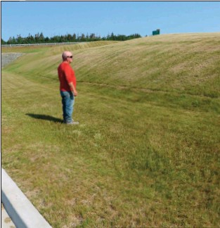 ??  ?? At the Galway site, Wayne Sinnott surveys banks of grass, hydroseeded last year. Hydroseeding of additional acreage continues this summer at the site.