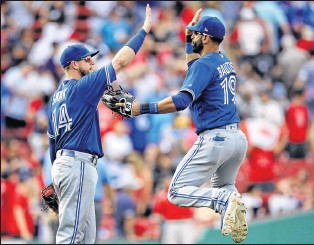 ?? AP PHOTO ?? Toronto Blue Jays right fielder Jose Bautista, right, leaps as he celebrates with first baseman Justin Smoak after defeating the Boston Red Sox in a game at Fenway Park in Boston on Thursday.