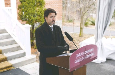 ?? JUSTIN TANG / THE CANADIAN PRESS ?? Prime Minister Justin Trudeau speaks at his daily press conference outside of his residence in Ottawa on Friday, where he voiced his hope that the first wave of COVID-19 would pass by the middle of summer.