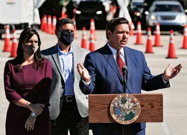 ?? JOE RAEDLE/GETTY IMAGES ?? Florida Gov. Ron DeSan­tis speaks last week about the open­ing of a COVID-19 vac­ci­na­tion site at the Hard Rock Sta­dium in Miami Gar­dens, Fla. Vac­ci­na­tions will be avail­able for res­i­dents 65 and older who can drive up in the park­ing lot.
