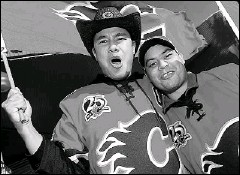 ??  ?? Reginald Tiangha and Michael Gilson show their team spirit outside of the Pengrowth Saddledome prior to the Calgary Flames' home-opener Saturday against the Edmonton Oilers.