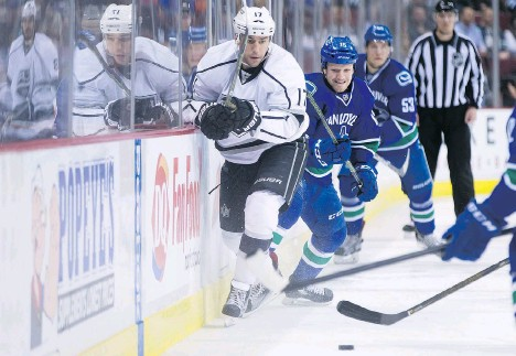 ?? DARRYL DYCK/THE CANADIAN PRESS ?? Los Angeles Kings forward Milan Lucic passes the puck while being pressured by Vancouver Canuck Derek Dorsett during the first period of at Rogers Arena on Monday Night. Dorsett registered an assist on Emerson Etem's late first-period goal.