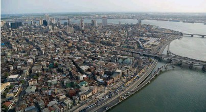 ??  ?? Previous spread: an aerial view of the Lekki Peninsula, southeast of Lagos, where the Lekki Free Trade Zone (LFTZ) is currently under construction This page, top: an aerial view of the Carter Bridge over Lagos Lagoon. The structure connects the financial district with the city to the north; bottom: the financial district of Lagos. With over 17 million inhabitants, this Nigerian metropolis is considered one of the world's most populous megacities