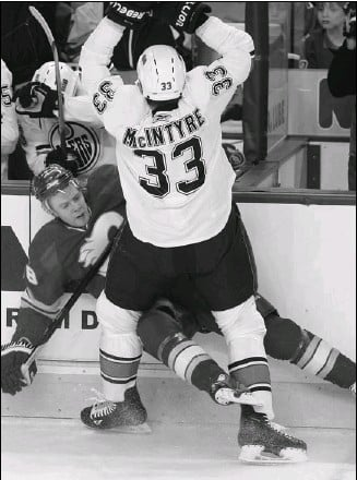 ?? colleen De Neve, calgary Herald ?? Calgary's Matt Stajan absorbs a big hit from Edmonton's Steve MacIntyre during Wednesday's NHL game at the Dome. The Flames won 6-1, but their playoff hopes died after Chicago and Anaheim victories.