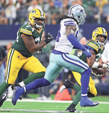 ?? RONALD MARTINEZ / GETTY IMAGES ?? Green Bay Packers guard Elgton Jenkins (74) looks to block downfield as running back Aaron Jones (33) carries the ball Sunday at AT&T Stadium in Arlington, Texas.