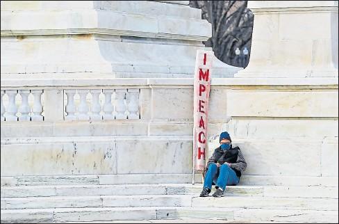 ?? SHAWN thew/efe ?? • Un hombre con un cartel que dice 'Impeach' (procesen) permaneció ayer a las afueras del Congreso, en Washington.