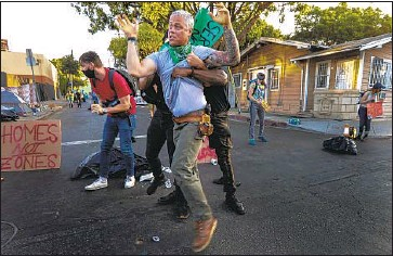 ?? Irfan Khan Los Angeles Times ?? DEMONSTRATORS RESTRAIN a man after he scuffled with other protesters blocking McCadden Place in Hollywood to resist a scheduled city cleanup that would have required homeless people to remove their tents.