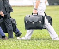 ?? REUTERS ?? A military aide carries the so-called nuclear football as he walks to board the Marine One helicopter with U.S. President Donald Trump for travel to Florida from the White House in 2019.
