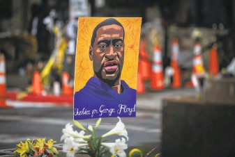 ?? Jason Armond / Los Angeles Times ?? A poster memorializes George Floyd last month near where he was killed by Officer Derek Chauvin in Minneapolis. Prosecutors argue that Chauvin deserves a severe prison sentence.