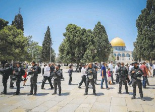 ?? (Jamal Awad/Flash90) ?? SECURITY FORCES guard a group of Jews during a visit to the Temple Mount on Tisha Be'av yesterday.