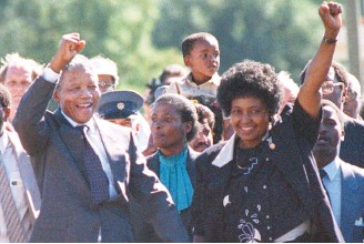 ?? AFP-Yonhap ?? Nelson Mandela, left, and his then-wife Winnie, right, raise their fists and salute cheering crowd upon Mandela's release from the Victor Verster prison near Paarl in this 1990 file photo. Winnie Mandela died in a Johannesburg hospital, Monday, after a...