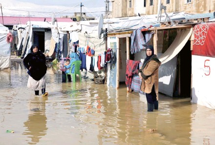 ??  ?? Syrian refugees stand in rainwater and mud in a settlement in Barr Elias.