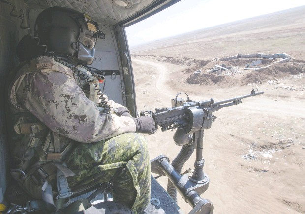 ?? Ryan Remior z / THE CANADIAN PRESS files ?? A Canadian Forces door gunner keeps watch as his Griffon helicopter goes on a mission in northern Iraq in 2017