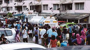 ?? FILE PIC ?? Residents at a flat in Ampang collecting water from a tanker during a water supply disruption last year.