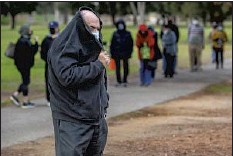 ??  ?? THE WAIT for a vaccination can be a cold, miserable day in the park. Above, Thomas Zisfain, 70, covers up at Balboa Sports Complex.