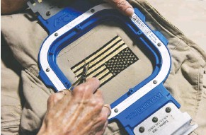 ??  ?? TOP: Workers print, fold and embroider clothing on the floor of Nine Line Apparel, a company in Savannah, Ga., that produces patriotic clothing. ABOVE: Mara Frizzell cuts threads off a coat that has just been embroidered with the American flag.