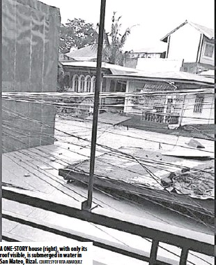 ??  ?? A one-st ory house (right), with only its roof visible, is submerged in water in San Mateo, Rizal. Courtesy of Rita Ab arquez